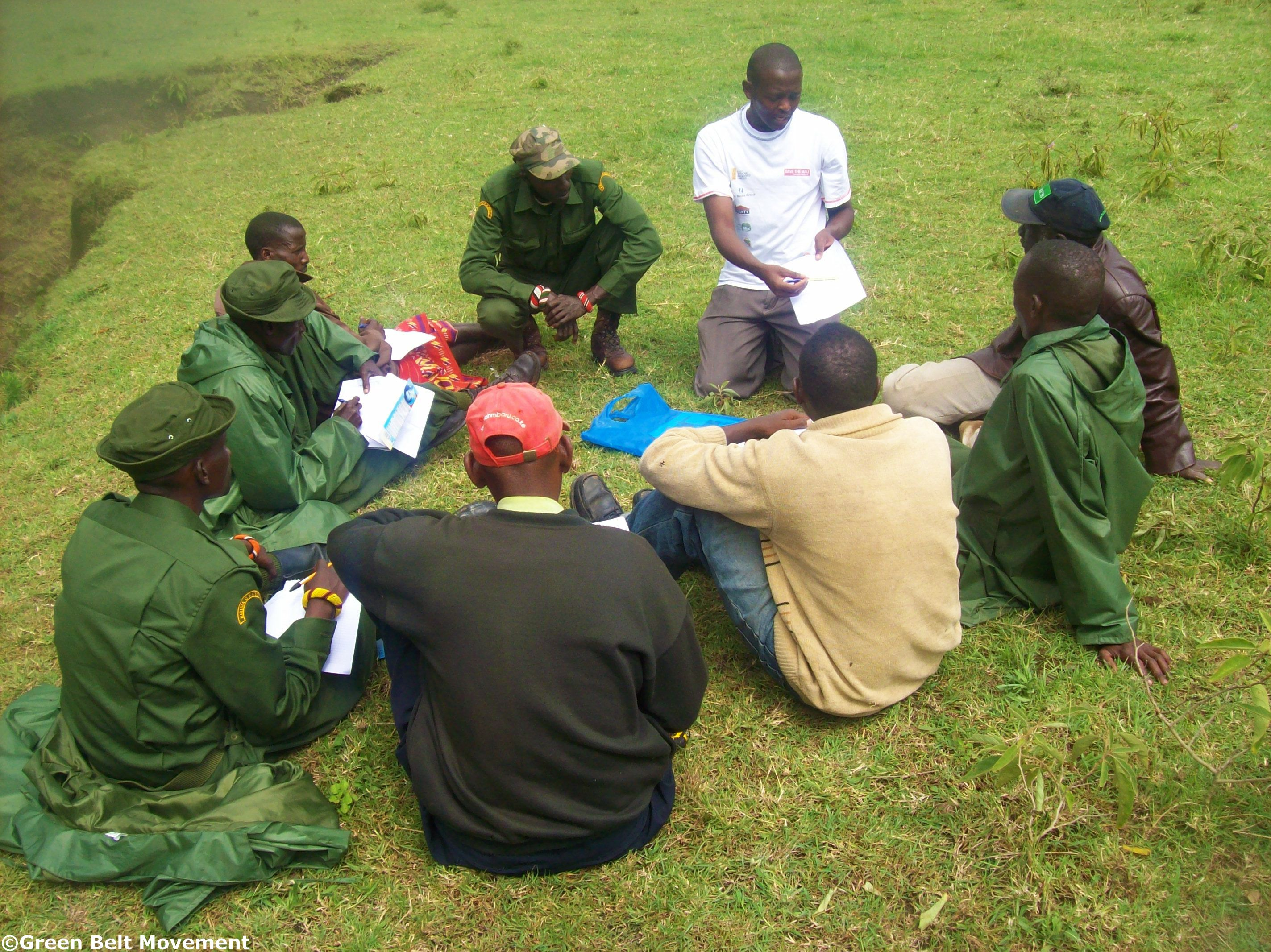 GBM's Joseph Munyao, a GIS and Remote Sensing Analyst (in white) teaches the GVs how to interpret mapping
