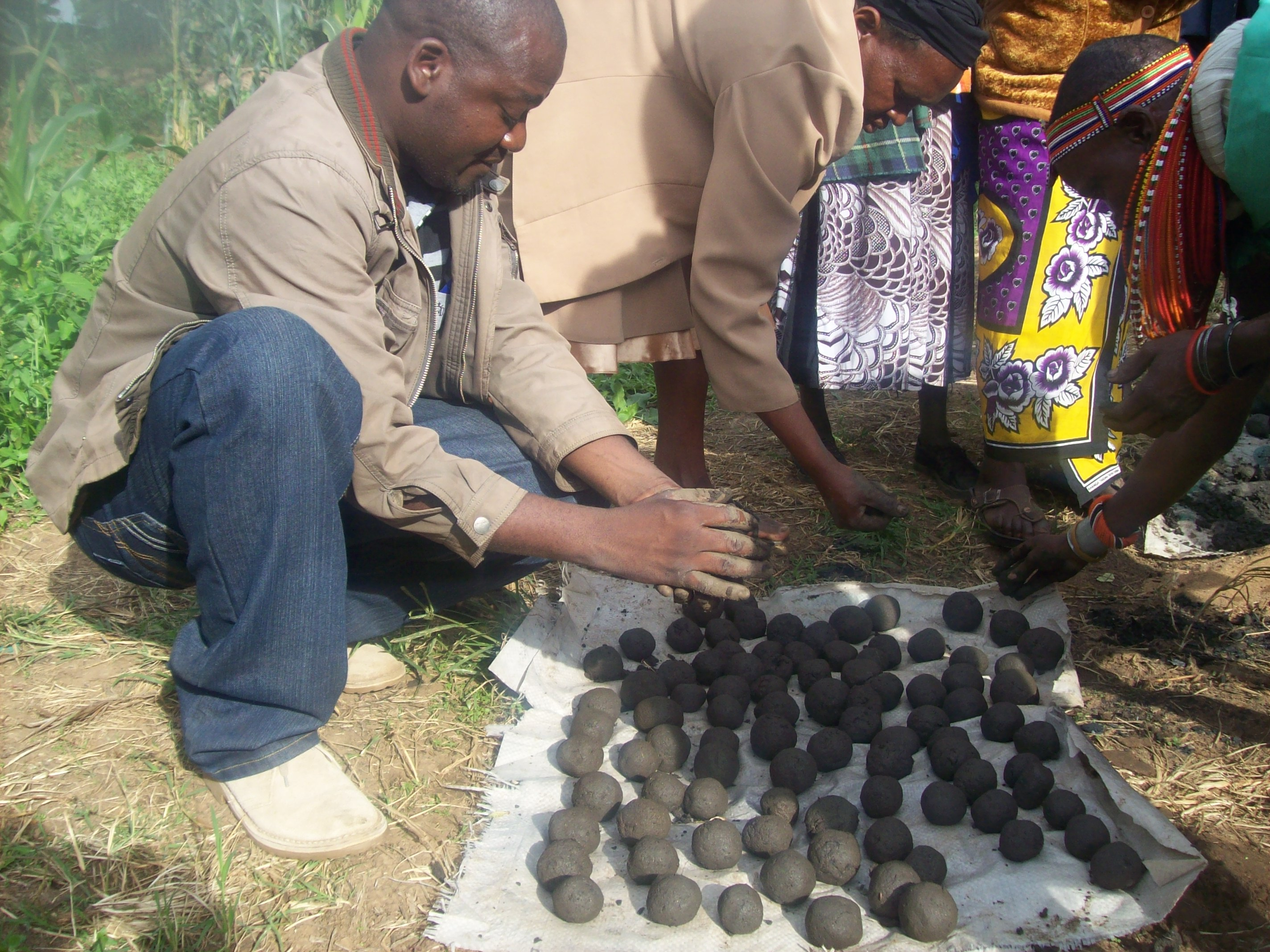GBM's project lead officer, Wycliffe Matika (Left) in Samburu rolling  mud  balls (refined Soil, charcoal dust and water in equal ratios) which are sundried for three days into fire briquettes depending on the weather patterns and put to use.