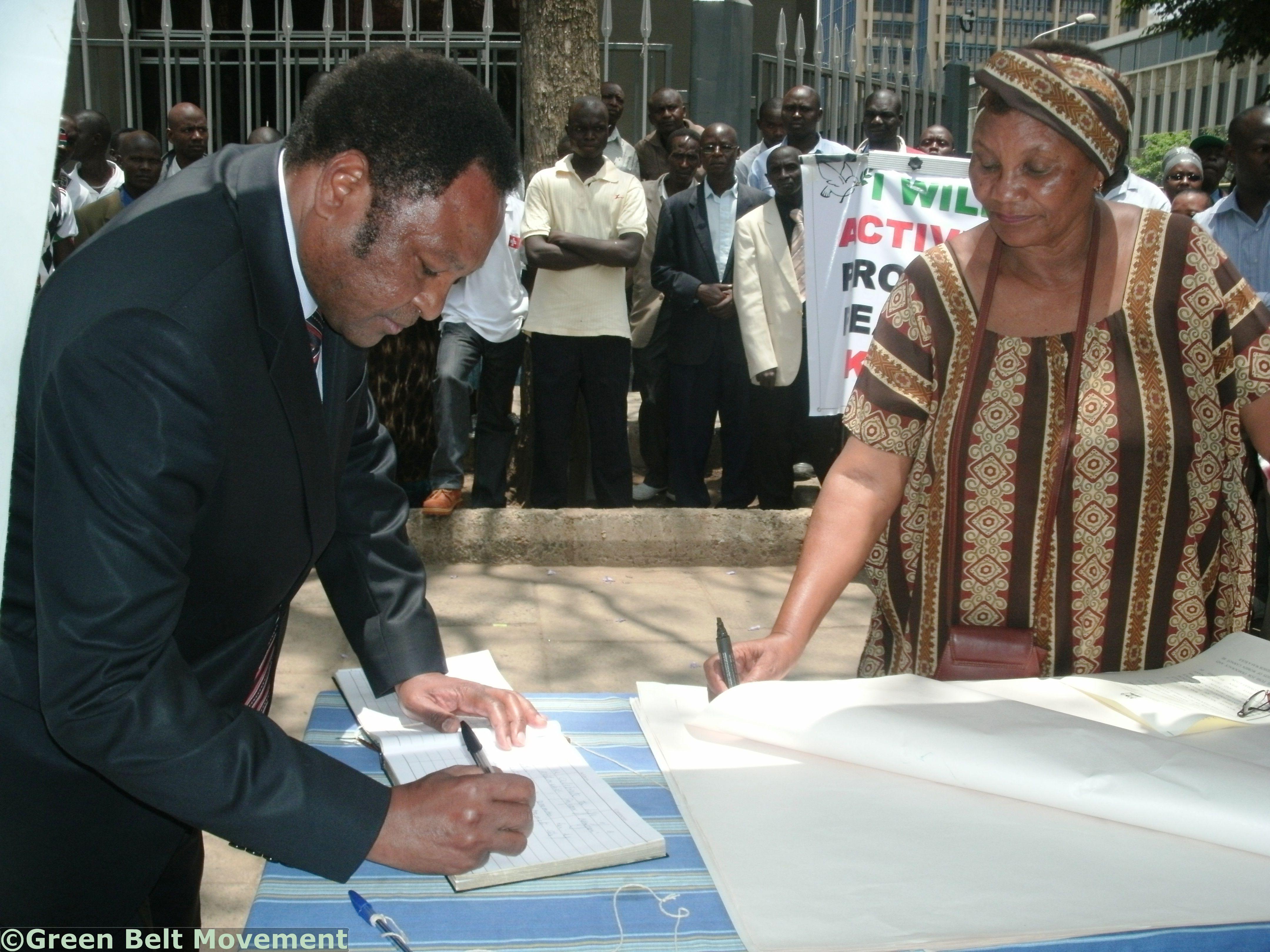 Provincial Commissioner for Nairobi, Mr. Njoroge Ndirangu, signs the pledge book.