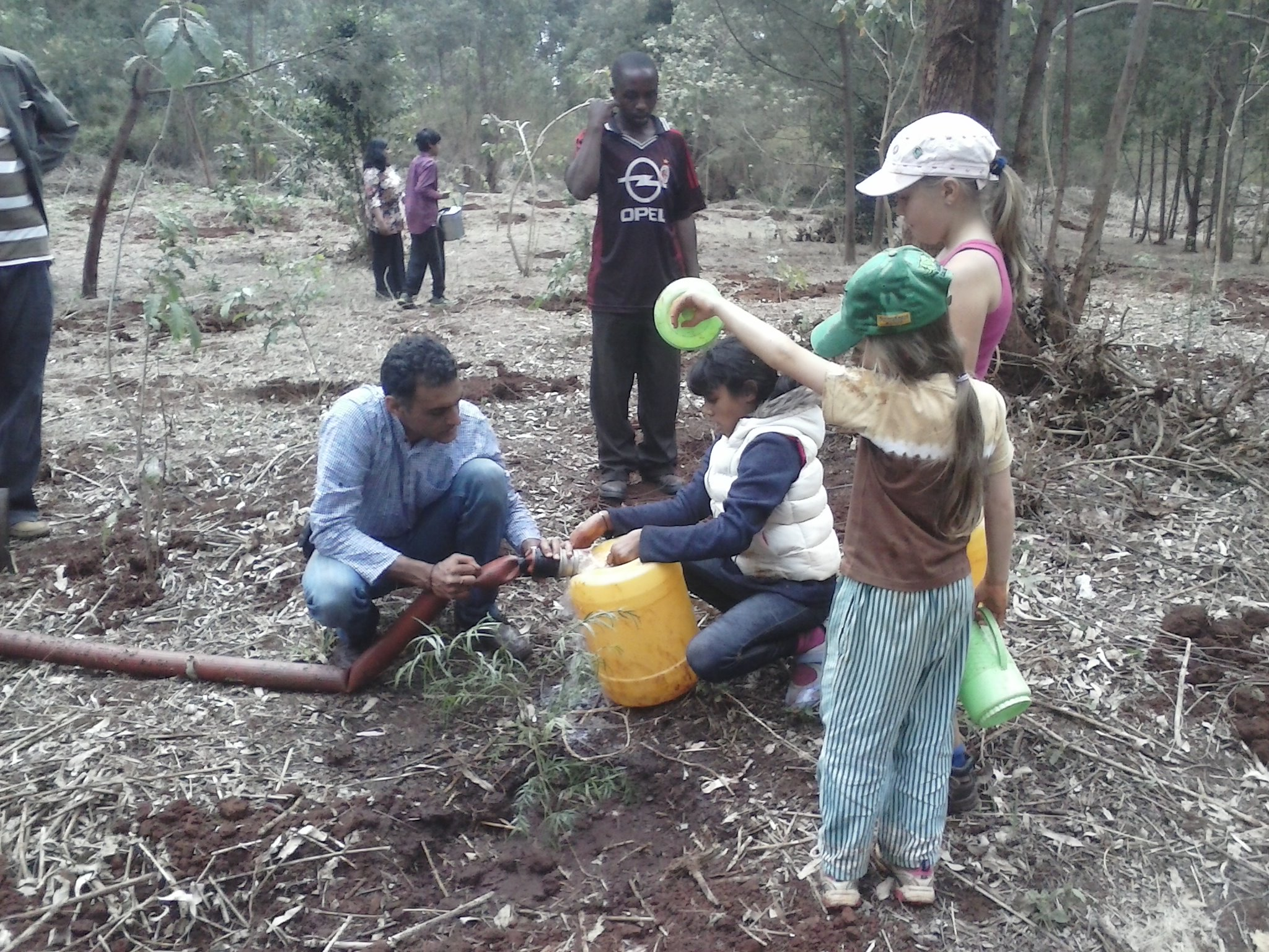 Parents and pupils fill water cans to water the planted trees on site.