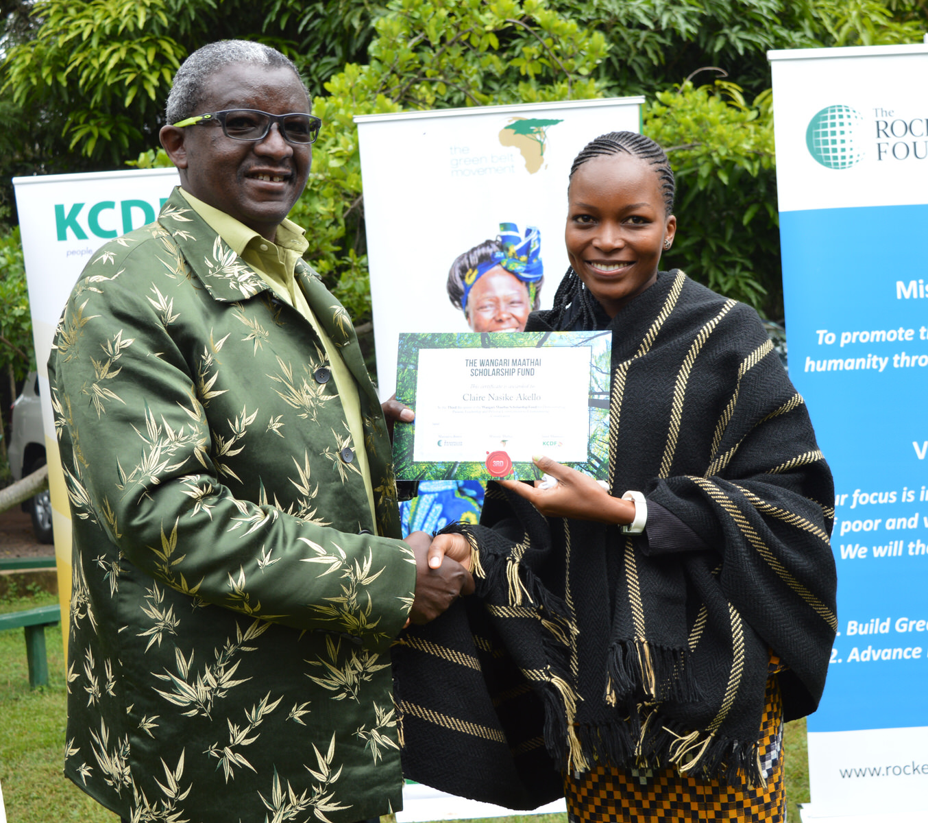Claire Nasike Akello receives her certificate from Dr. Isaac Kalua, founder of Green Africa Foundation