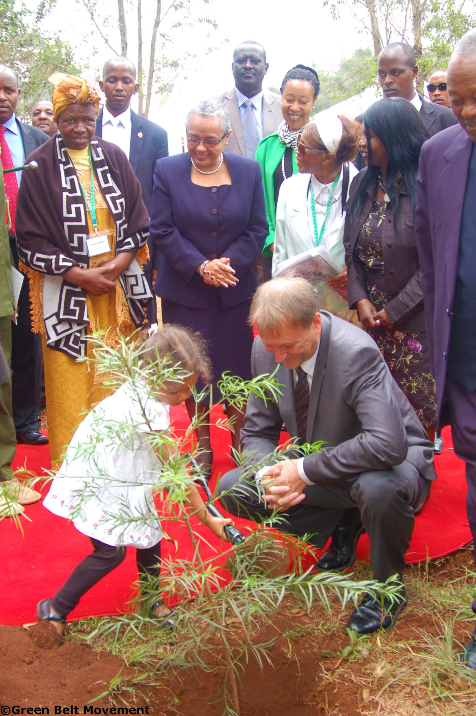 From left to right: GBM Honorary Treasurer Mrs Lillian Wanjiru Njehu, First Lady Margaret Kenyatta, GBM Board Member Prof. Vertistine Mbaya and Cabinet Secretary, Ministry of Environment, Water and Natural Resources Prof. Judi Wakhungu look on as Ruth Wangari Lindkvist, granddaughter to Wangari Maathai plants a commemorative tree in Karura Forest during the 2nd memorial anniversary