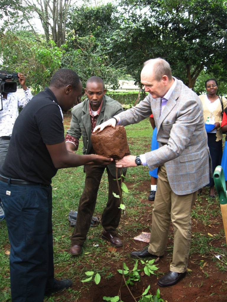 Sir John Peace being assisted by GBM Project Officer Edwin Ngungiri and Senior Programme Officer Charles Peter Mwangi in planting the tree