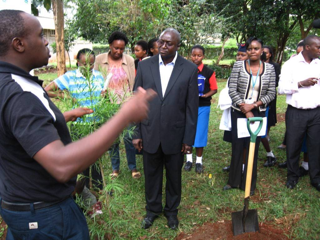 Senior Programme Officer, Charle Peter Mwangi explaining to the Mr. Iamin Manjang CEO of the Standard Chartered Bank the steps to be undertaken before planting the tree, the type and its significance